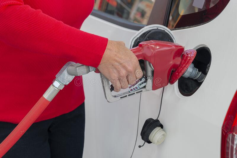 Woman's Hand Pumping Gasoline Into Her Car royalty free stock photo