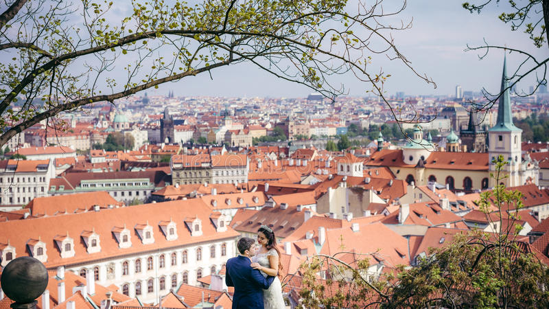 Horizontal close-up view of the happy hugging newlyweds at the background of Prague panorama. royalty free stock images