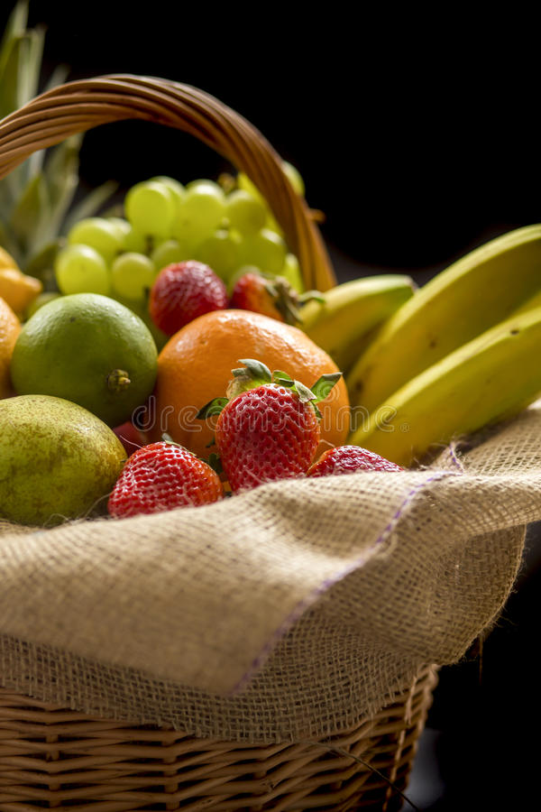 Horizontal Closeup detail on a basket full of fruit on a dark background stock photography