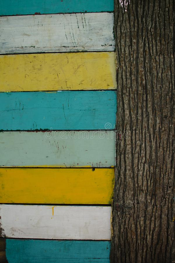 Horizontal colored boards and vertical tree trunk summer stock photography