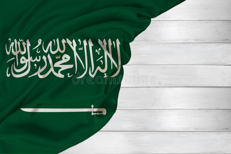Horizontal colored national flag of modern state of Saudi Arabia, beautiful silk, white wood background, concept of tourism,. Economy, politics, emigration stock photo