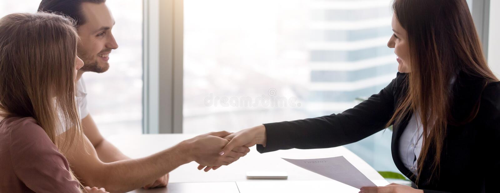 Horizontal image couple signing real estate contract handshaking with realtor stock photography