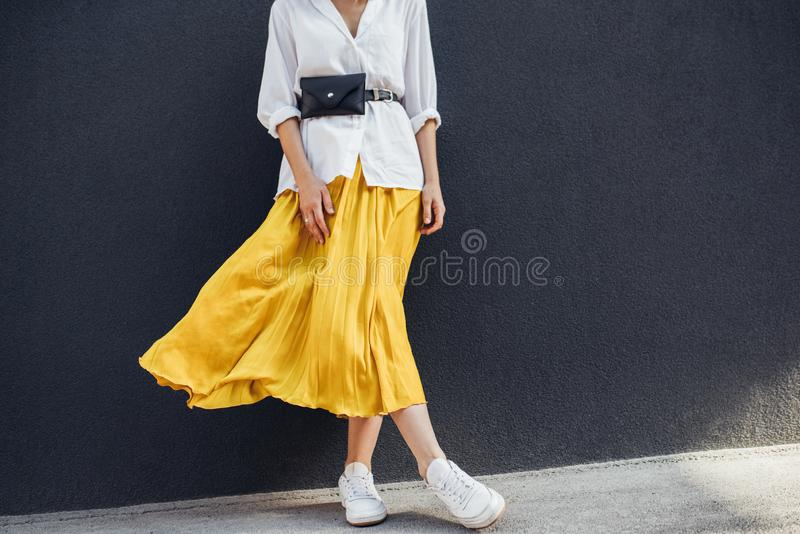 Horizontal cropped body image of beautiful slim woman in beautiful yellow skirt. Caucasian female fashion model standing over gray. Wall background outdoor with stock photos