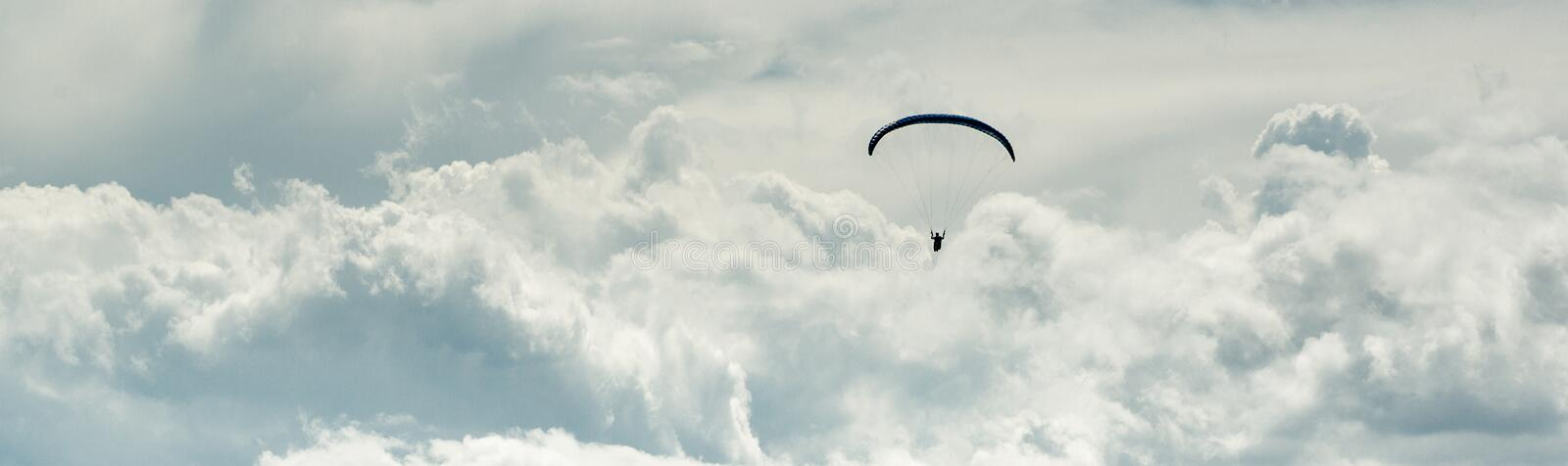 Horizontal cropped image paraglider over cloudy sky background royalty free stock image