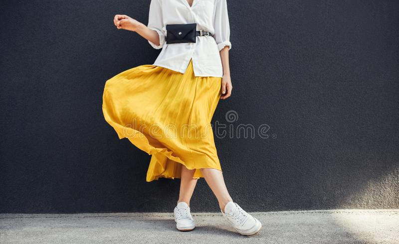 Horizontal cropped image of stylish slim woman in beautiful yellow skirt. Caucasian female fashion model standing over gray wall. Background outdoor with copy stock images