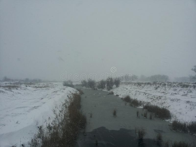 Horizontal de l'hiver Une petite rivière parmi une tempête de neige d'hiver Carte postale avec une rivière en hiver Basse tempéra images libres de droits