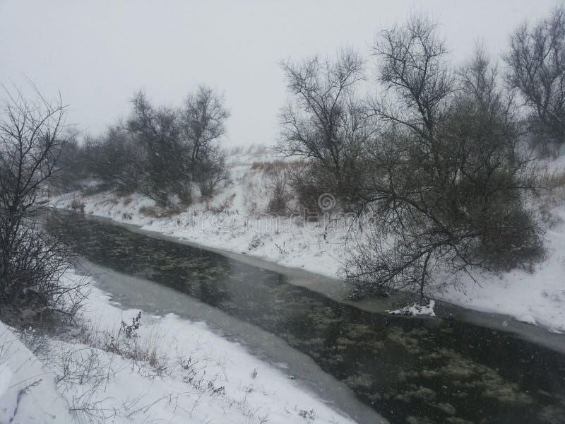 Horizontal de l'hiver Une petite rivière parmi une tempête de neige d'hiver Carte postale avec une rivière en hiver Basse tempéra images stock