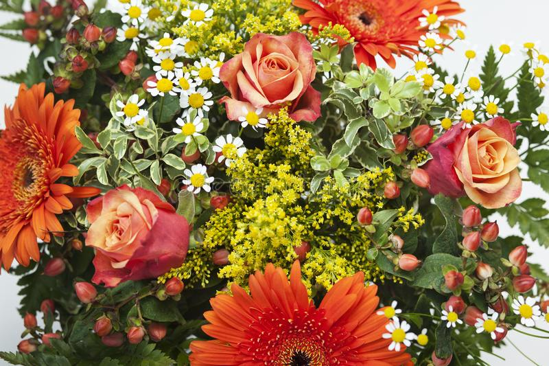 Detail shot of a bouquet of orange, yellow and red flowers in a vase. royalty free stock photography
