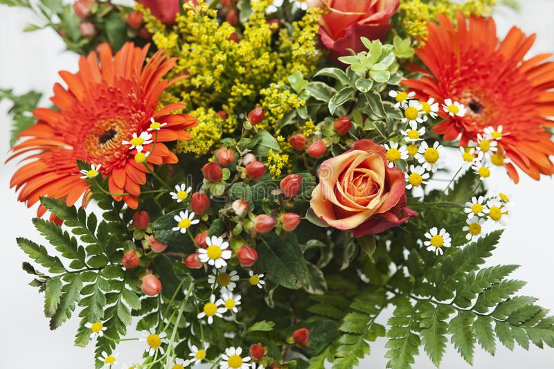 Detail shot of a bouquet of orange, yellow and red flowers in a vase. stock images