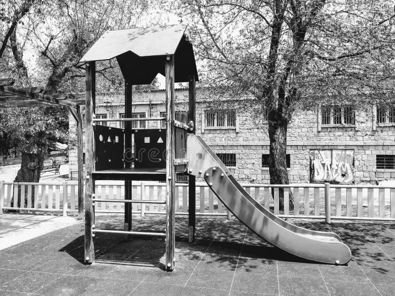 Horizontal en noir et blanc Une glissière en parc photos stock