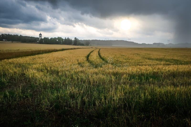 Horizontal excessif Le coucher du soleil et la pluie au-dessus d'un ` s d'agriculteur mettent en place photographie stock