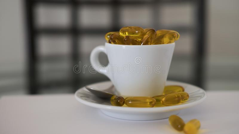 White ceramic coffee cup, and saucer with oily dietary supplement capsules over spilling royalty free stock photography