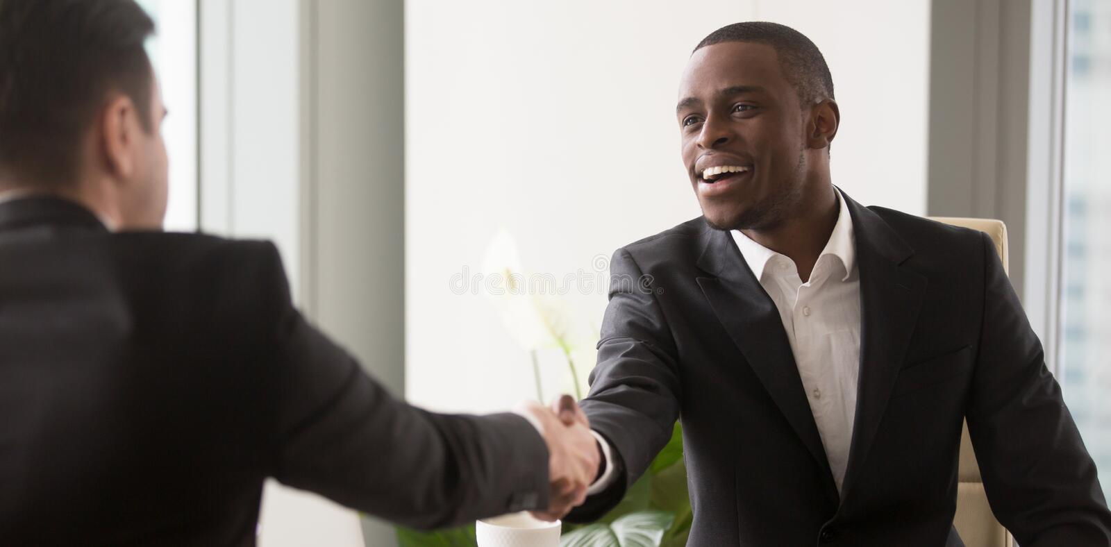 Horizontal image black and caucasian businesspeople starting negotiations shaking hands stock photo