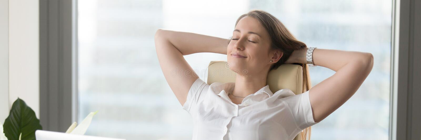 Horizontal image businesswoman sitting on chair resting put hands behind head. Horizontal photo businesswoman sitting on chair put hands behind head feels good stock photography