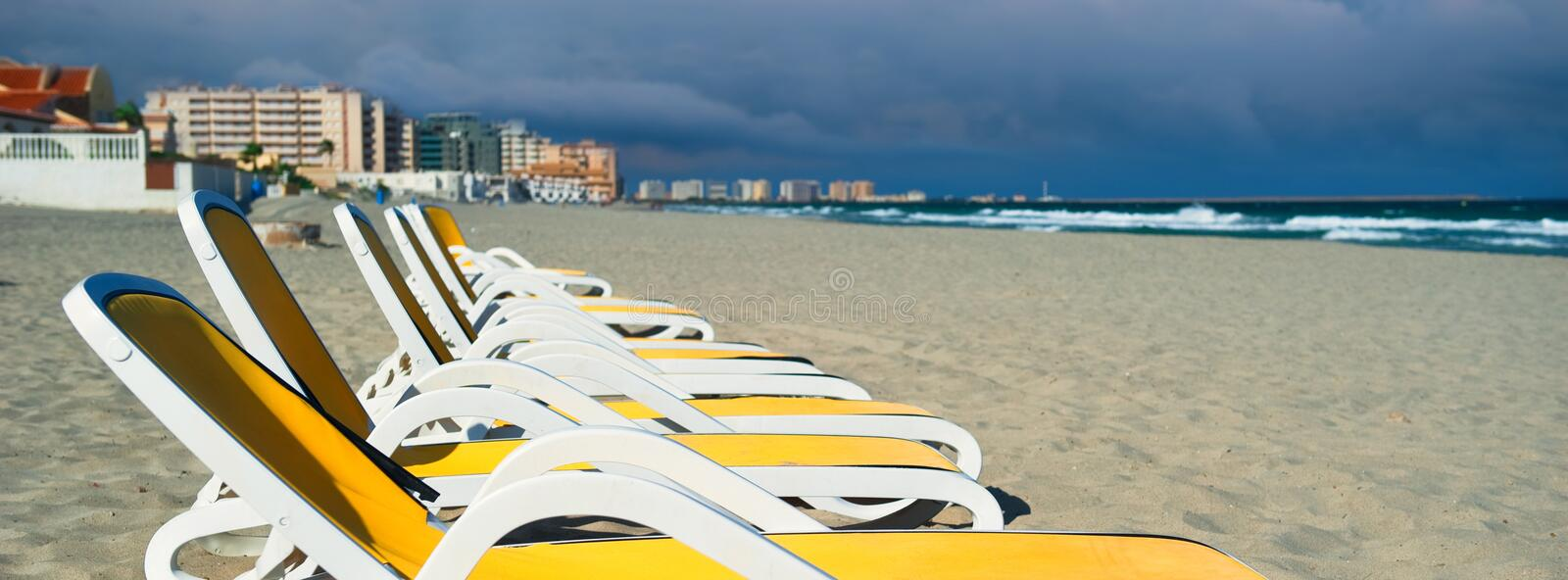Horizontal image cropped view yellow blue color empty sunbeds deck-chairs in a row on the sandy beach, La Manga del Mar Menor stock photography