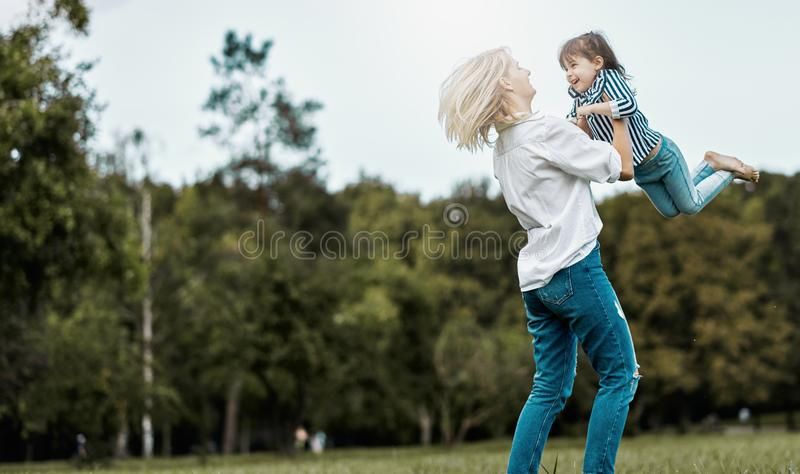 Horizontal image of cute happy little girl playing with her beautiful mother in the park. Happy family time together. Positive. Emotion. Good relationship royalty free stock image