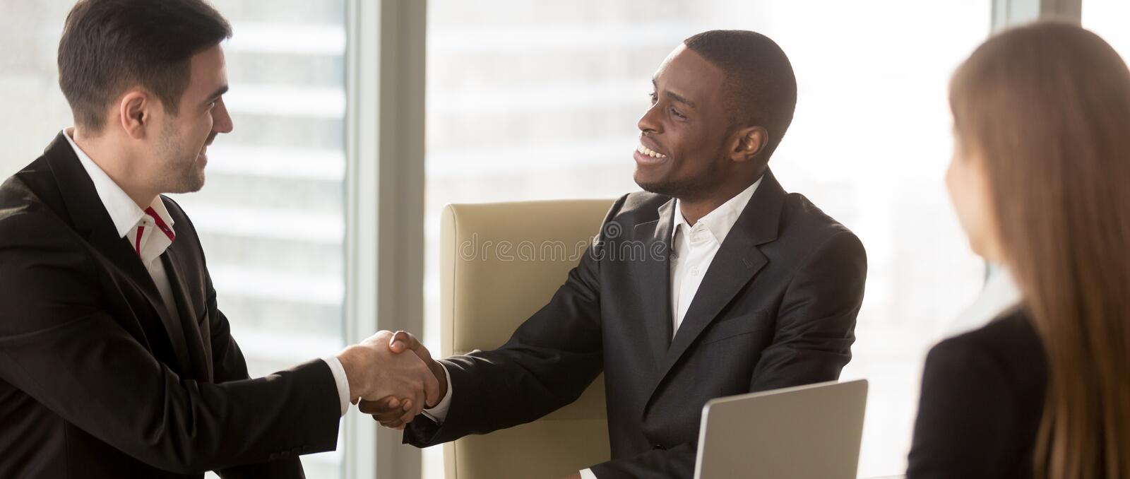 Horizontal image diverse people meets at office boardroom shaking hands royalty free stock image
