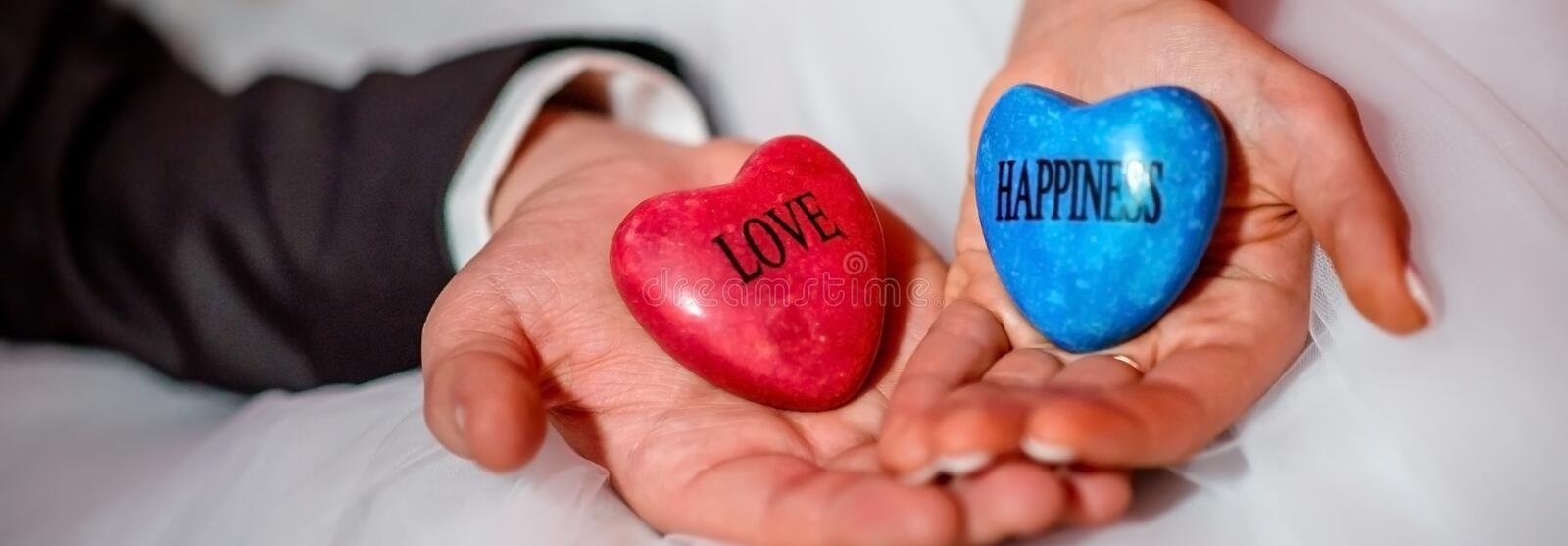 Horizontal image hands of bride and groom holding stones with love and happiness words. Hands of bride and groom holding stones with love and happiness words royalty free stock photo