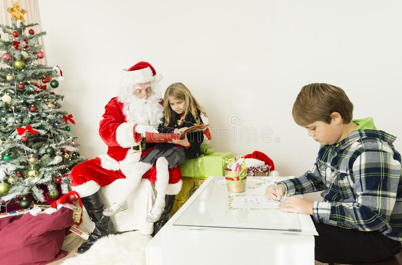 Santa claus with kids reading a book royalty free stock images