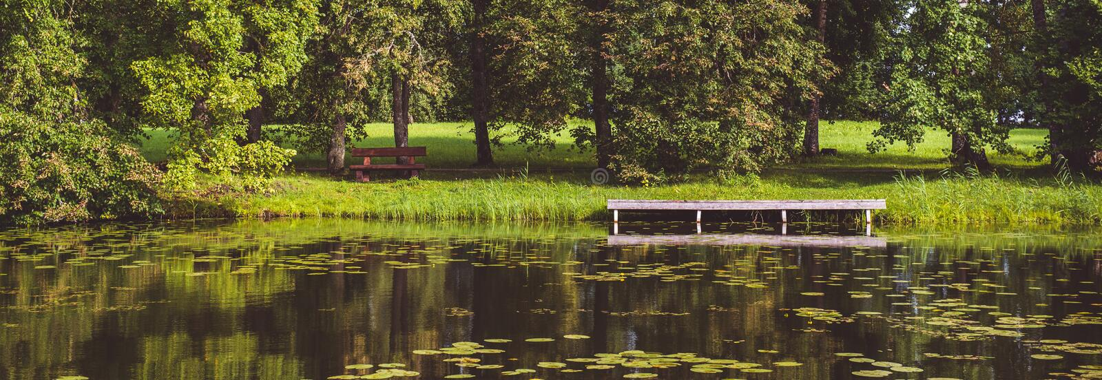Horizontal image panoramic scenic view summer green landscape with picturesque forest lush lawn wooden pier dock for boats. In pond lake mirrored reflected royalty free stock image