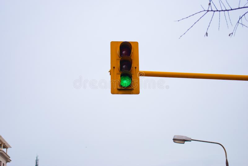 Horizontal image of the traffic lights against the sky. Laconic urban picture of the green light switched on the traffic light placed high over the road royalty free stock photography
