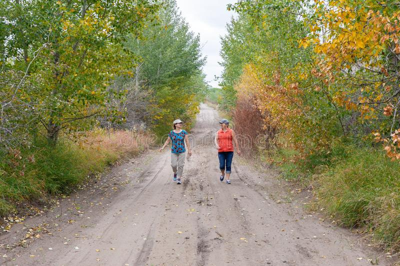 Two caucasian women walking down a rural road. Horizontal image of two caucasian ladies walking down a rural country road in the fall time talking and laughing stock photo