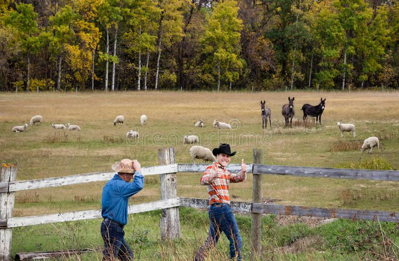 Two caucasian farm cowboys walking by a fence acting silly. royalty free stock image