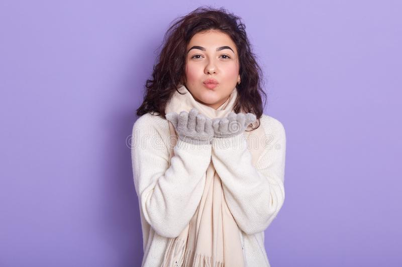 Horizontal indoor shot of emotional charming сute brunette standing isolated over lilac background in studio, wearing white royalty free stock photo