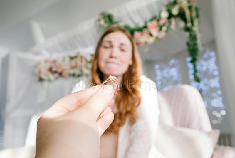 Man giving ring to woman. Horizontal indoors shot of hand of a person proposing to happy woman stock photos