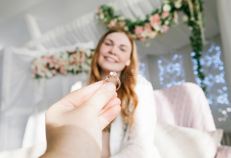 Man giving ring to woman. Horizontal indoors shot of hand of a person proposing to happy woman stock images