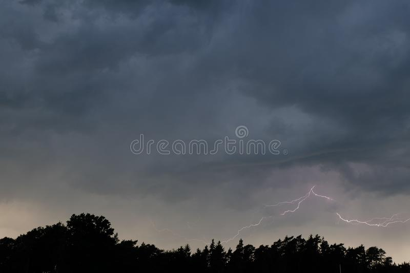 Horizontal Lightening Bolt. A horizontal lightening bolt illuminates from a thunderstorm shelf cloud behind and above a dark evening forest in Bavaria Germany royalty free stock photography