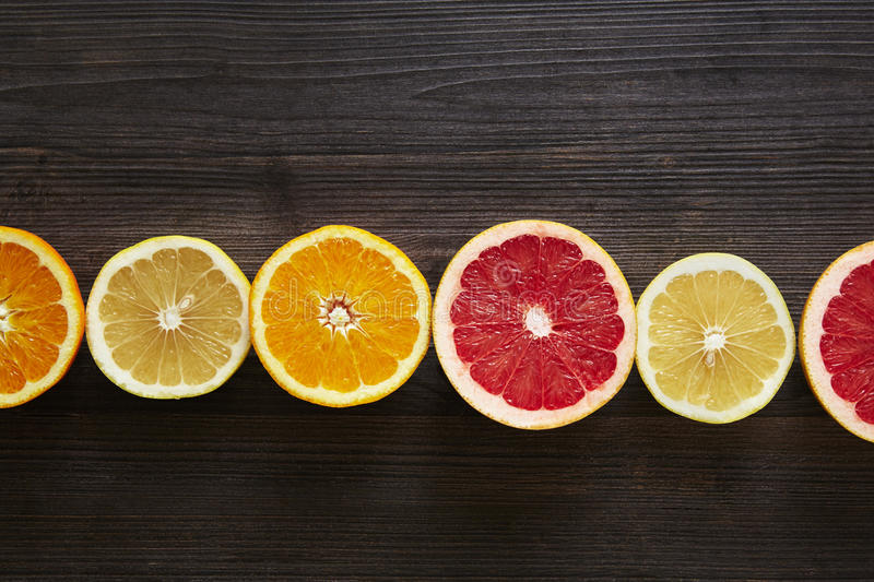 Horizontal line of sliced citrus fruits stock image