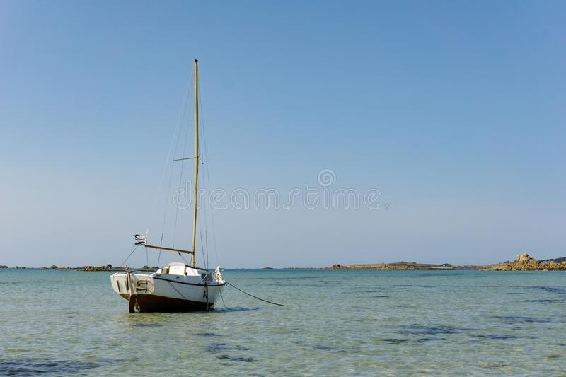 Horizontal ocean coast and beach landscape with small sailboat under a blue sky royalty free stock photo