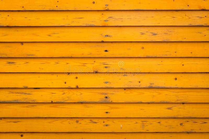 Horizontal old wood fence background. Old wooden planks with yellow paint stock photo