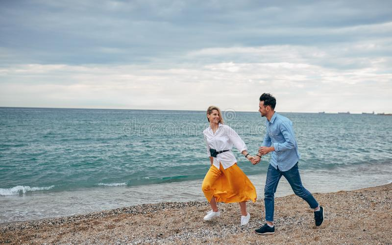 Outdoor shot of happy smiling couple walking on beach. Young handsome man and beautiful woman strolling together on seashore stock images