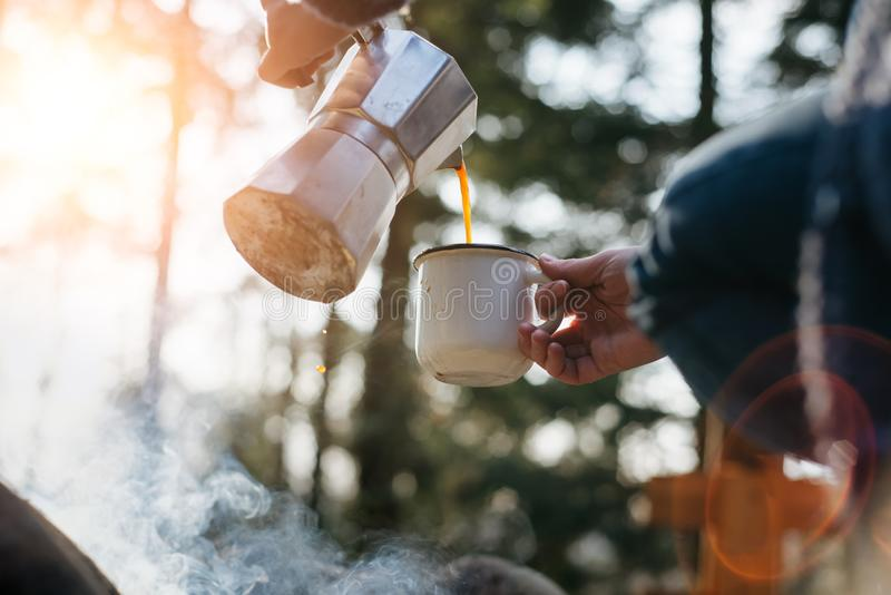 Horizontal outdoors image of young woman pours itself hot beverage in mountains near to bonfire . Girl sitting and holding a mug of coffee after hiking. Travel royalty free stock photography
