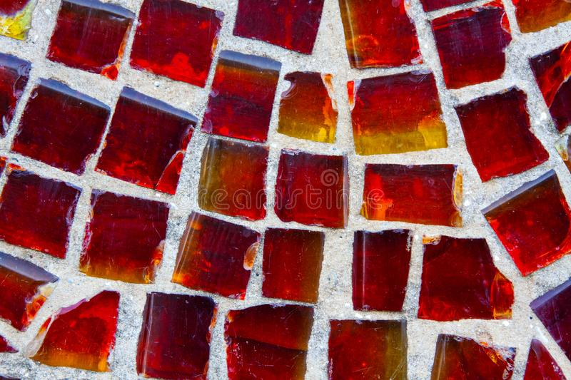 Horizontal pattern of red street mosaic. Background from red-orange glass mosaic. Beautiful bright background from a red mosaic stock photo