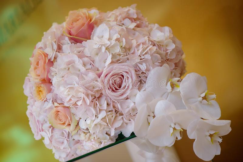 Classy floral arrangement in a pastel round bouquet featuring pink hydrangea roses and orchids stock image
