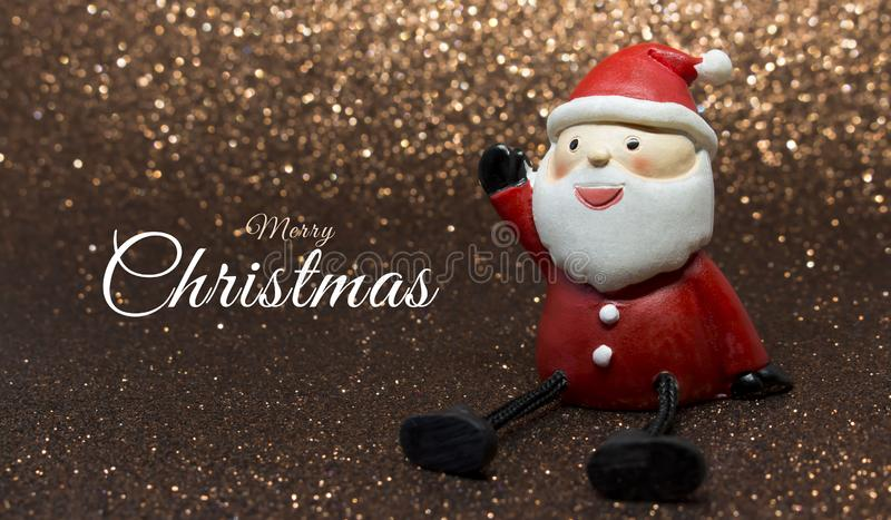 Adorable santa claus doll on golden glitter background with white Merry Christmas text to the left. Horizontal photo of an adorable santa claus doll on golden royalty free stock images