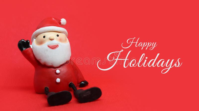 Adorable santa claus doll on red background with white Happy Holidays text to the right. Horizontal photo of an adorable santa claus doll on red background with stock photo