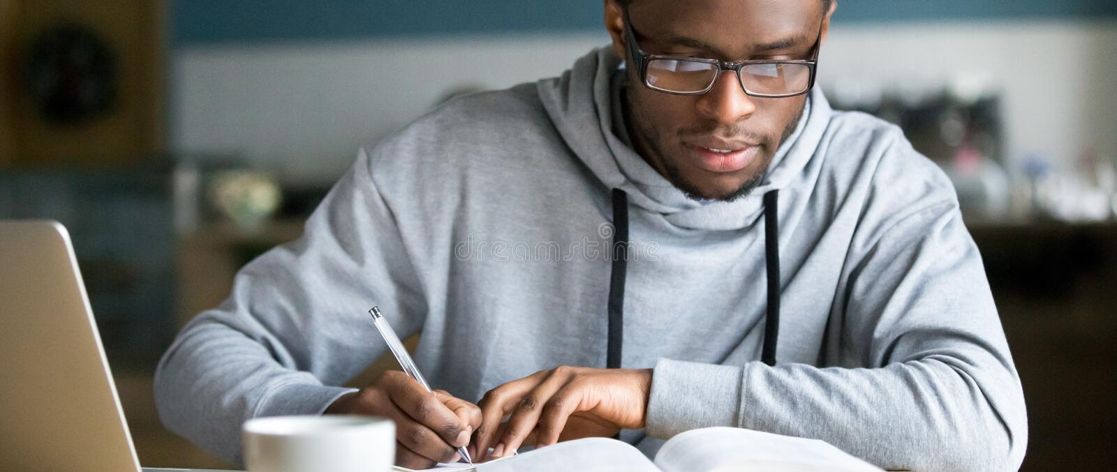 Horizontal photo african student study writing using book and computer. Closeup smart millennial african student wear glasses hold pen noting writing down royalty free stock photos
