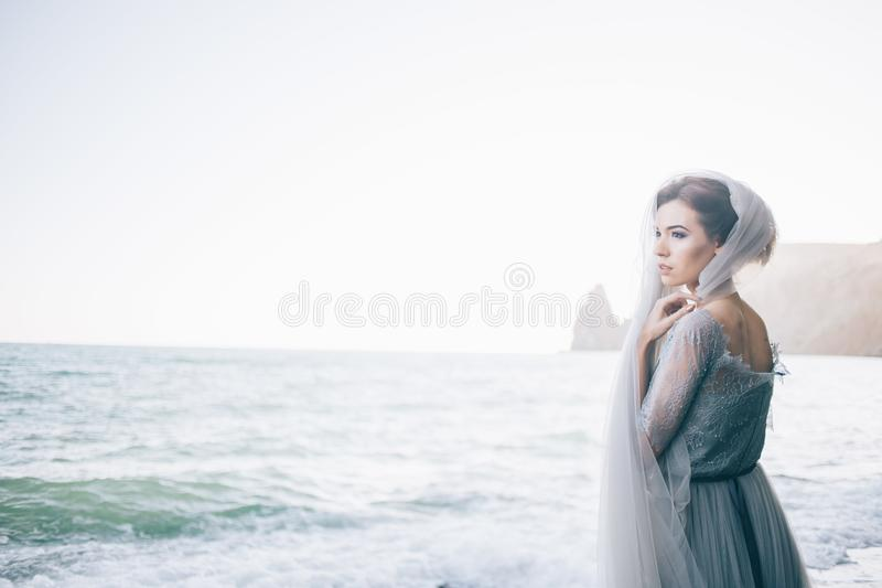 Horizontal photo of a beautiful bride woman on the beach. Fine art, copy space. Wedding inspiration stock photography