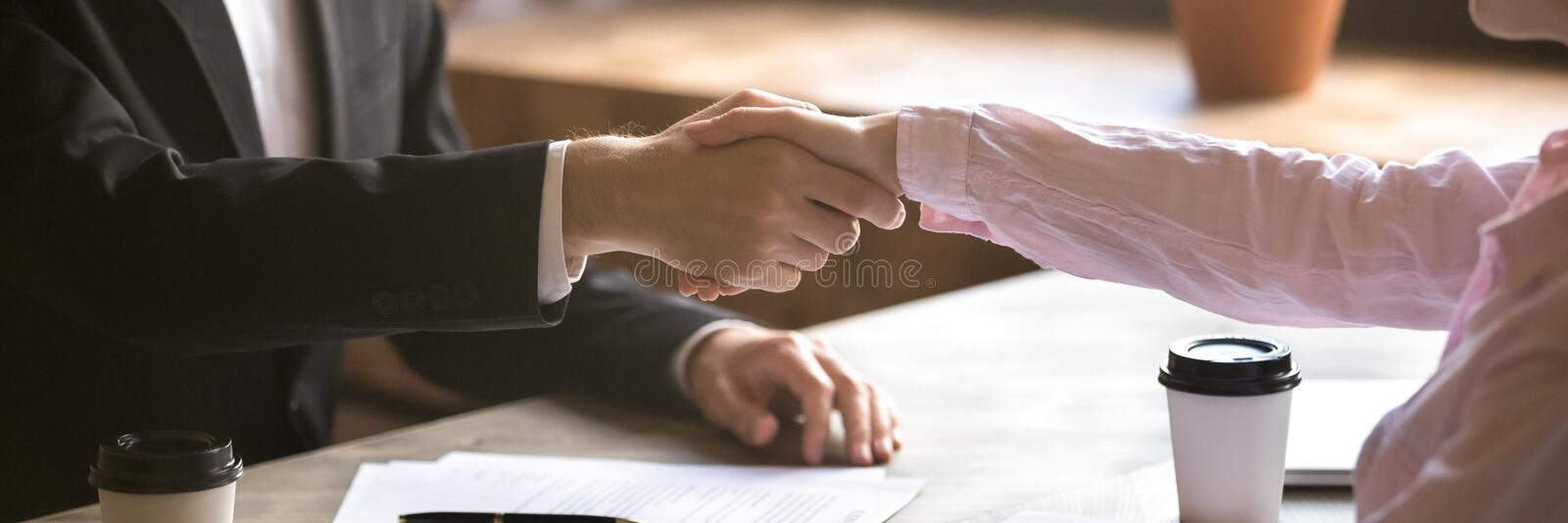Horizontal photo closeup hands of businessman and businesswoman shaking hands. Horizontal photo close up hands two people businessman businesswoman shake hands royalty free stock photo