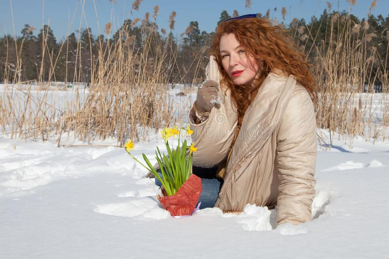 Charismatic pretty woman sitting in snowdrift and holding her coat collar royalty free stock photos