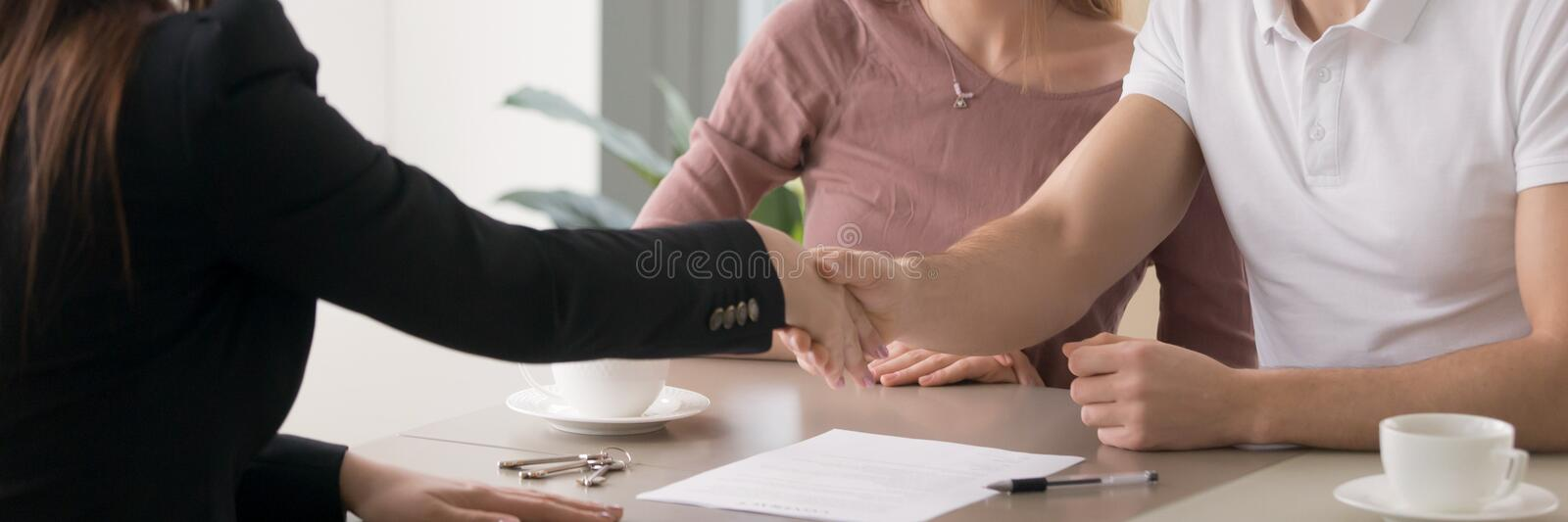 Horizontal photo couple signing real estate contract handshaking with realtor. Horizontal concept photo married couple meeting at office with realtor agent stock photo