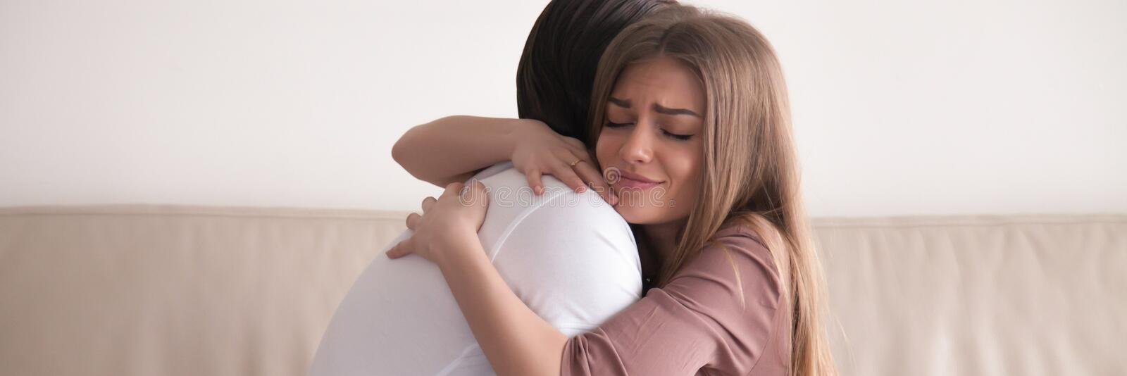 Horizontal photo couple sitting on couch hugging reconcile after quarrel. Horizontal photo couple in love sitting on sofa hugging reconcile after quarrel. Asking royalty free stock photography