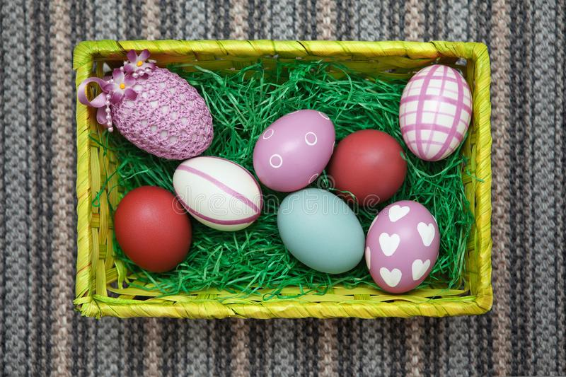 Horizontal photo of an Easter nest / Easter basket with colorful pastel eggs. stock image