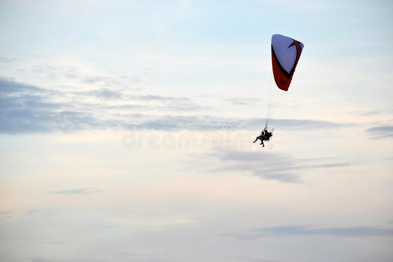 Horizontal photo of the flight of two people on a paraglider in a clear slightly cloudy sky in the summer. Colors are blue, red, white, black. Russia, Pskov royalty free stock photos