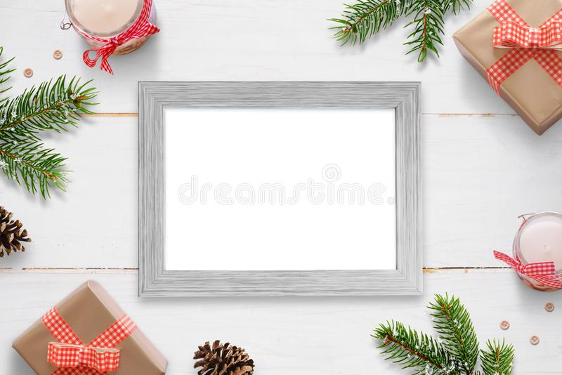 Horizontal photo frame surrounded with Christmas New Year gifts, tree branches and decorations. Isolated frame for photo mockup royalty free stock photography