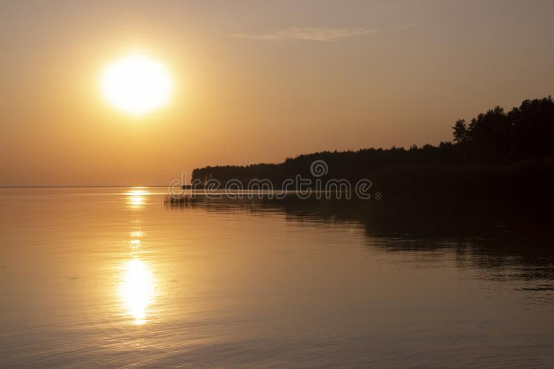 The  horizontal photo of golden sunset above the river or sea. Reflection in the water stock photos